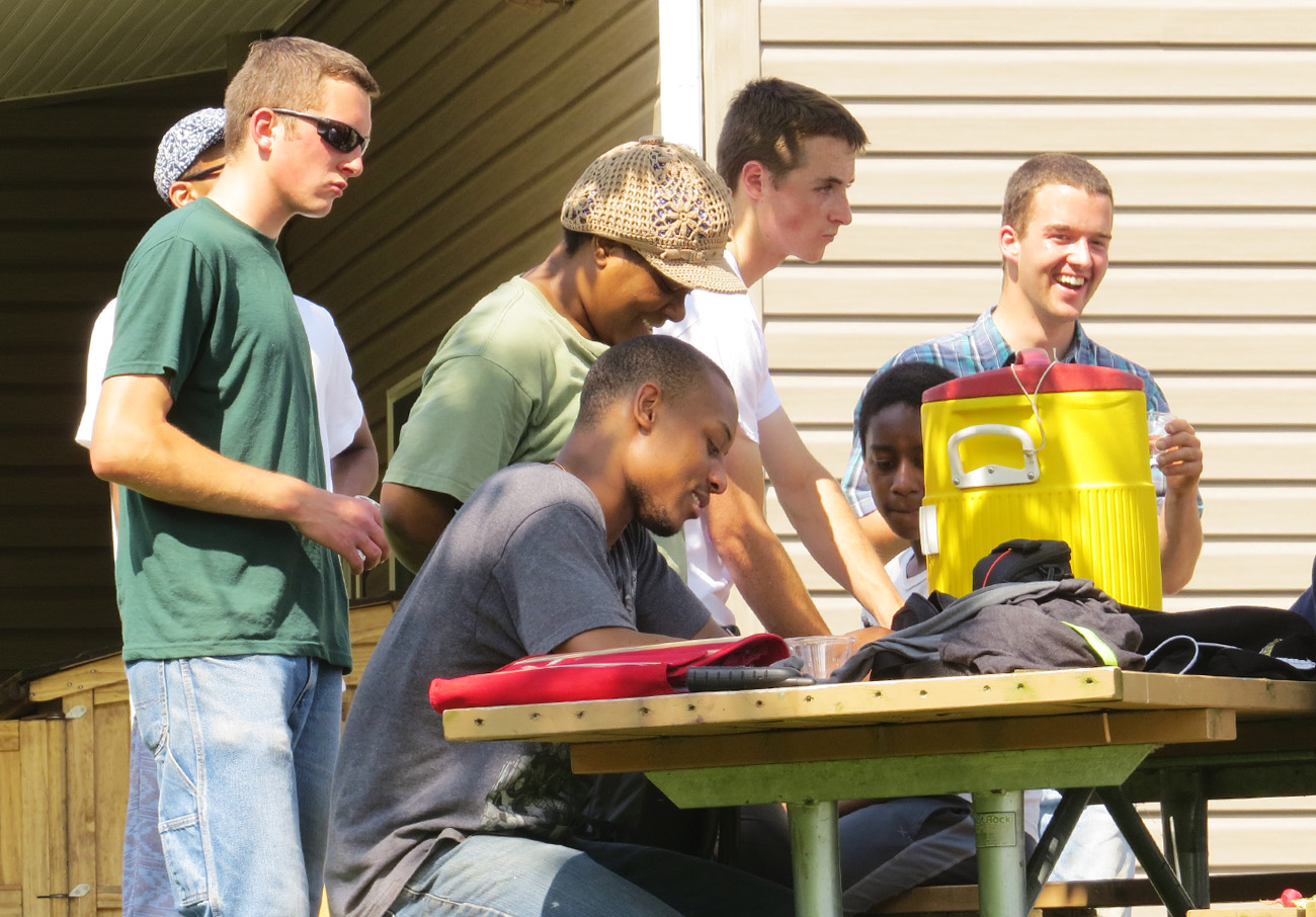 Young people around a table outdoors talking and laughing together