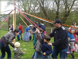 adults and children winding the ribbons of a maypole at the Holzland community