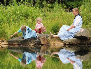 a teacher sitting outdoors and watching as two young girls play by a pond