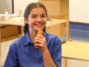 a girl enjoying her snack of carrots