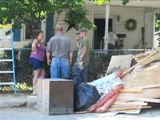 Bruderhof volunteers talking with a homeowner outside her flood-ruined house in West Virginia