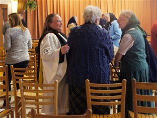 People talking together in the dining hall at the Woodcrest Bruderhof during the Unity Service