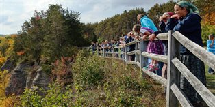 children and adults looking at autumn scenery
