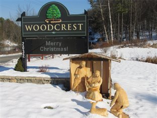 a sign on the Woodcrest Bruderhof Driveway that says Merry Christmas with a wooden Nativity scene below