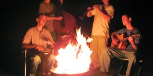 four men playing guitar, drum, clarinet and double bass outdoors around a campfire