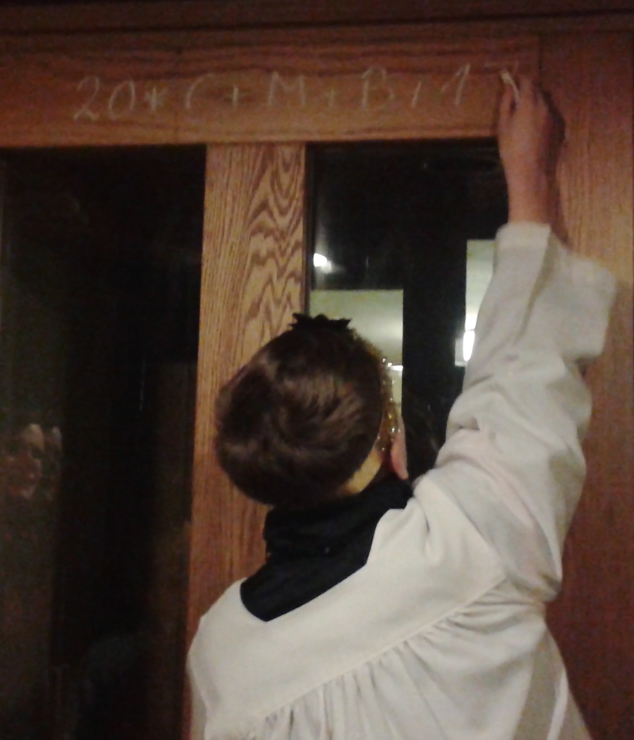 the blessing being written on the door frame by one of the star singers