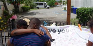 mourners standing together at a memorial outside of the Mother Emanuel AME church in Charleston, SC