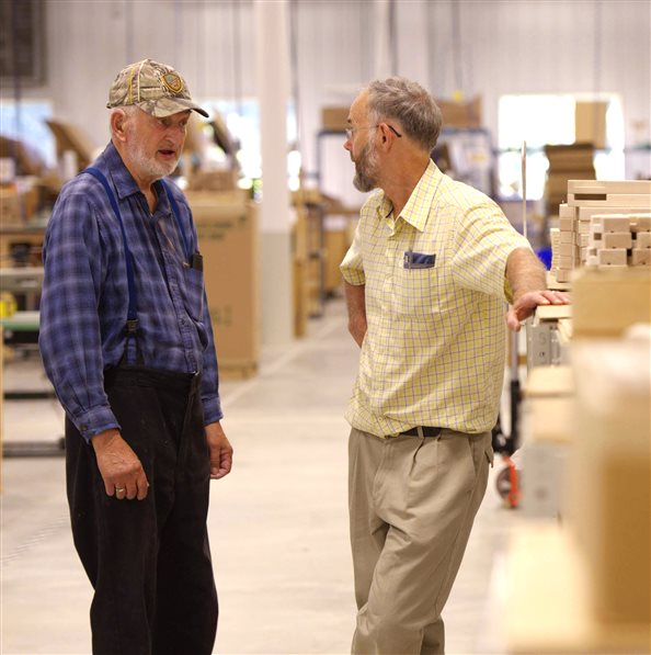 Two men talking together in a Community Playthings Woodshop