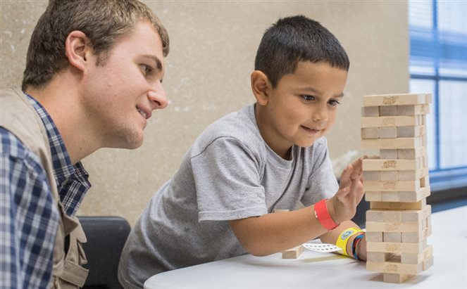 A little boy playing Jenga with a volunteer at a hurricane shelter in Texas