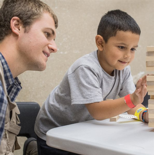 A young child playing Jenga with a volunteer at a hurricane shelter in Texas