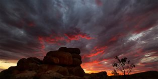a stormy sunset sky with some big boulders almost silhouetted in front