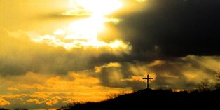 a cloudy sunset sky over a cross silhouetted on a hilltop