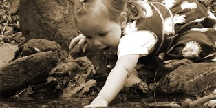 Rebekah's grandniece playing with pebbles in a stream