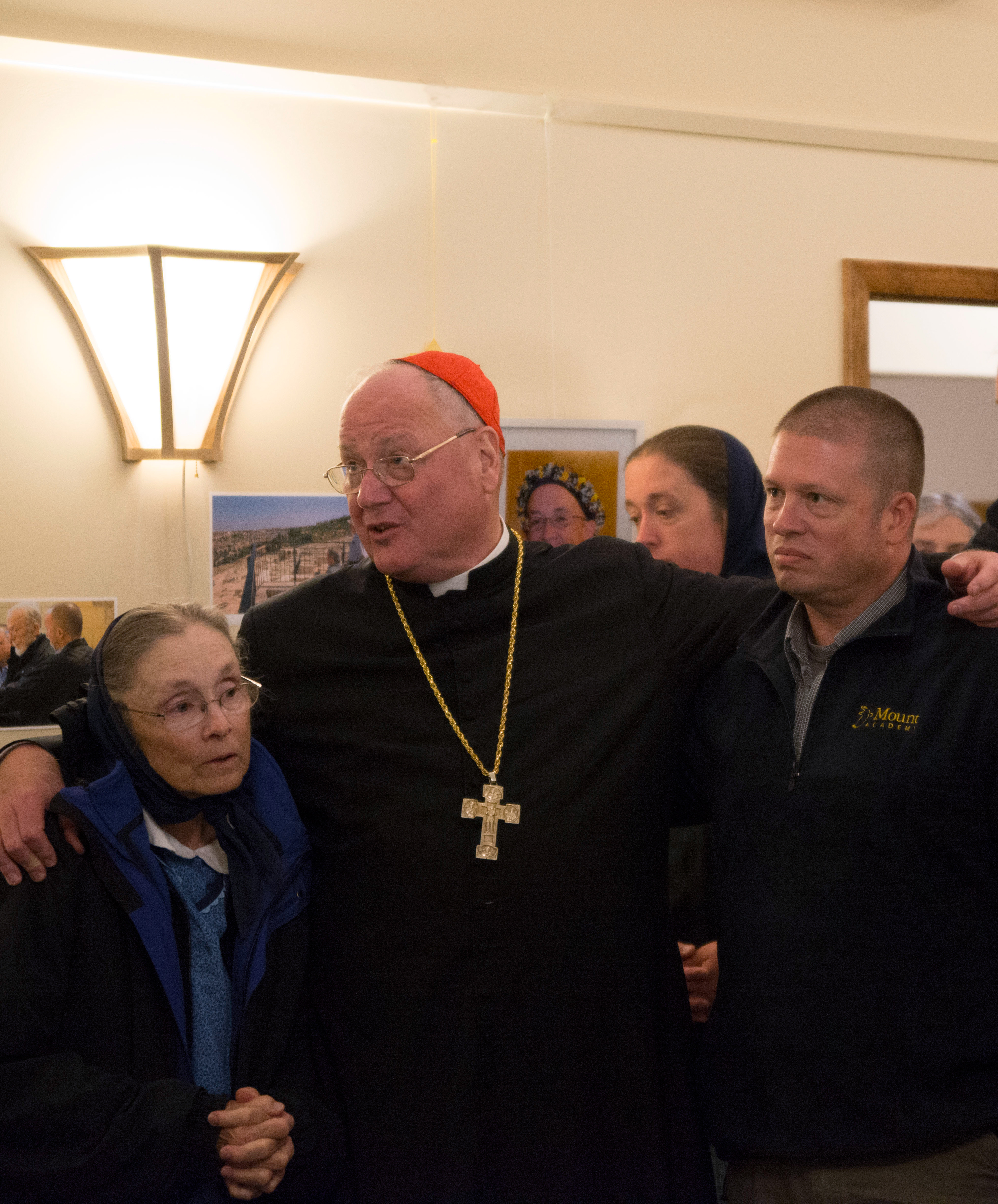 Cardinal Dolan praying with Christoph Arnold's widow Verena and son Heinrich