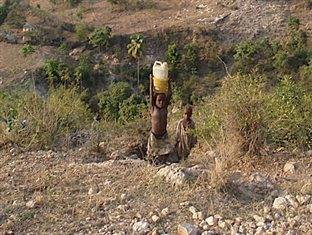 two young children carrying a water jug in Haiti