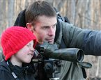 Darius Clement instructing his son how to look through a spotting scope