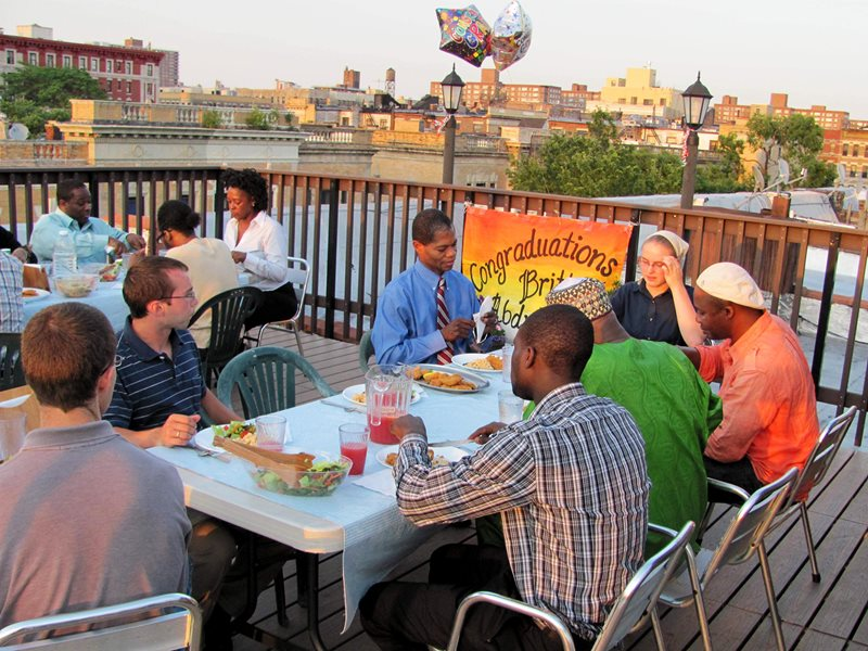 Members of the Harlem House community sharing a meal on their rooftop with some of their neighbors
